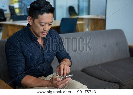Business executive using mobile phone in office