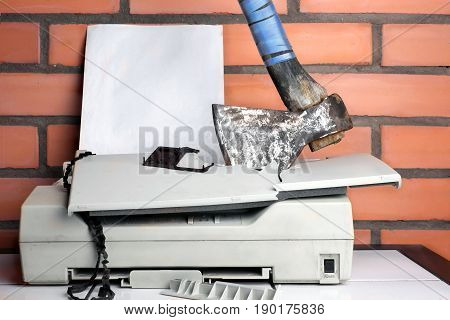 A blank paper sheet in a printer smashed with axe concept of aggression and bureaucracy