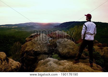 Sportsman With Red Baseball Cap And In White Jacket On Rocky Peak. Dreamy Fogy Landscape, Beautiful