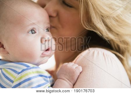 Caucasian mother kissing baby