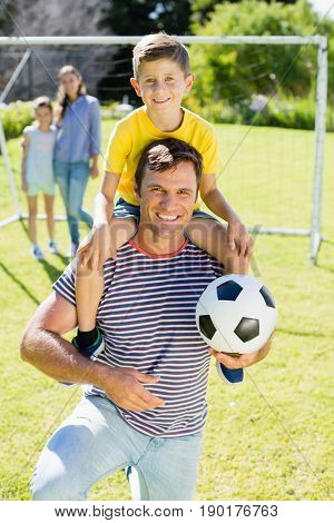Portrait of smiling father with football carrying his son on shoulder at the park