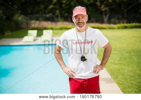 Portrait of swim coach with stopwatch standing with hands on hip near poolside on a sunny day