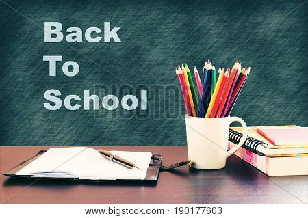 Back to school concept with books and color pencil on wooden table and written on blackboard.