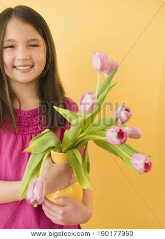 Mixed race girl holding vase of flowers
