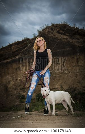 Brutal, bold girl with a fighting dog breed of bull terrier on a background of a rock in the evening