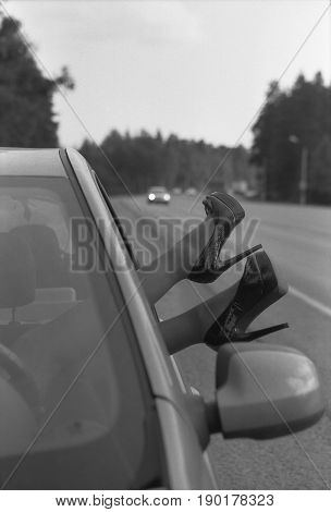 Female feet in high-heeled shoes stick out of the car. Black and white photo. Attention! The image contains the graininess of the photographic film!