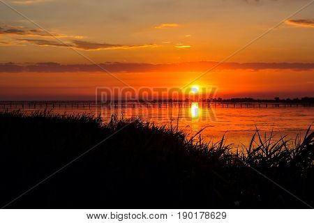 Sunset lake river landscape. Golden natural sky water sunset view of jetty or small bridge at horizon and orange sky above it with awesome sun golden reflection on calm waves as a background.