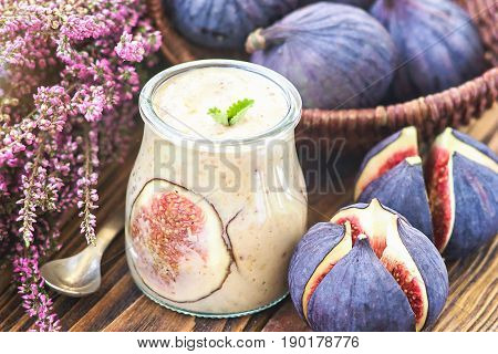 Beautiful healthy appetizer figs fruit smoothie or milk shake in glass jar with fresh figs, top view. Natural detox. Liquid ice cream. Yogurt cocktail dessert on wooden background, selective focus.