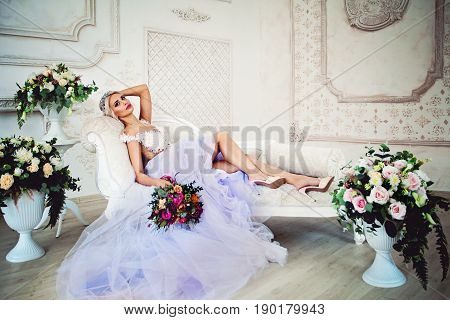 Beautiful Sexy Model Woman in Evening Gown with Tulle Skirt Relaxing on the Sofa