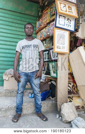 Young African male street vendor selling art pieces in the market. Abidjan, Ivory Coast, Circa May 2013.