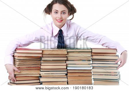 Young funny girl sitting at the desk with books . Isolated on white