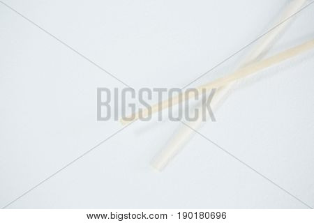 Chopsticks on a chopstick rest against white background