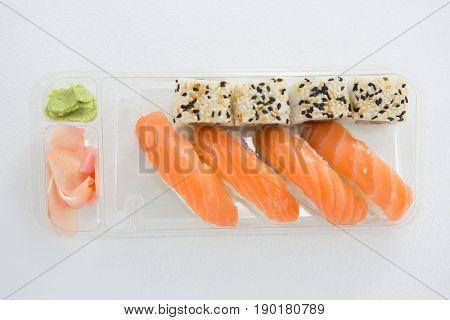 Plate of nigiri and uramaki sushi on white background