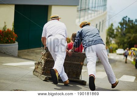 Toboggan Riders Moving Cane Sledge Downhill On The Streets Of Funchal, Madeira Island