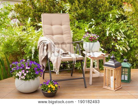 garden chair and table on terrace flowers  bush