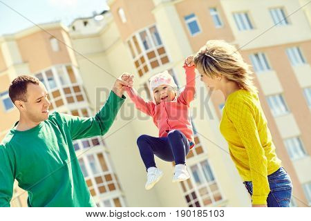 happy playing family outdoors. young parents with a baby for a walk in the summer. Mom, dad and child