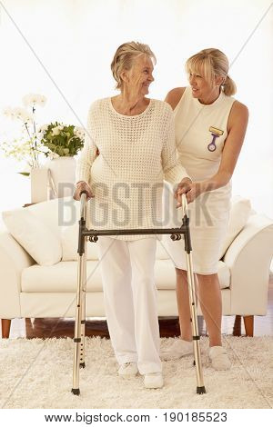 Older Caucasian woman and caregiver using walker in living room