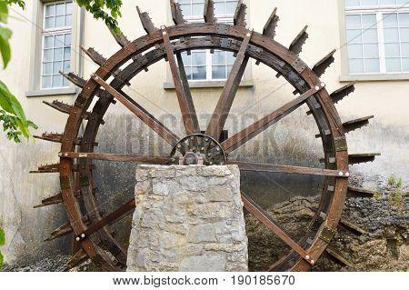 wooden water wheel beside house in Rhine Switzerland