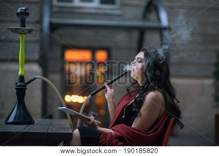 pretty girl sitting in a cafe and hookah smokers use tablet