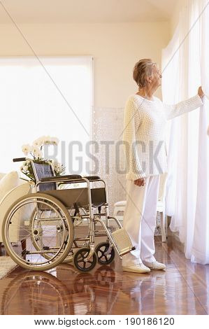 Older Caucasian woman standing by empty wheelchair