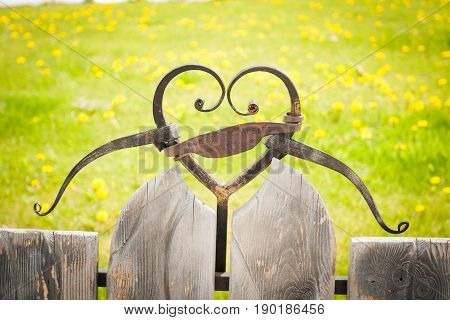 View Of Heart Of Forged On Bench With An Inscription Romeo And Juliet 1592 On Grass Background In Sunny Day.