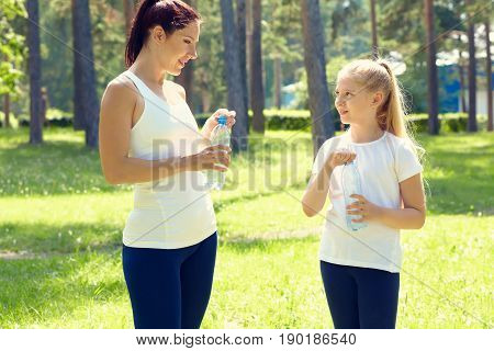 sporty mother and daughter. woman and child training in the park. outdoor sports and fitness. healthy sport lifestyle