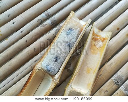 Glutinous rice roasted in bamboo joints, Thai dessert, on wooden background.