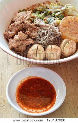 rice vermicelli topping pork ball and meat in brown soup with chili sauce