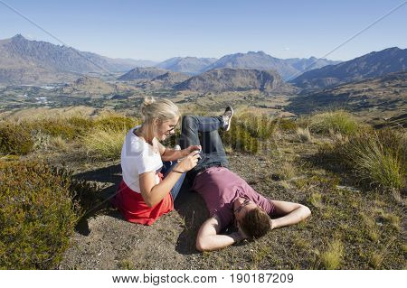 Caucasian couple taking pictures on rural hilltop