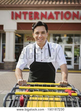 Hispanic worker pushing carts outside grocery store