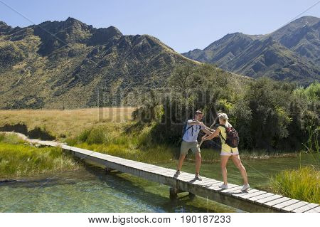 Caucasian couple on wooden bridge in rural landscape