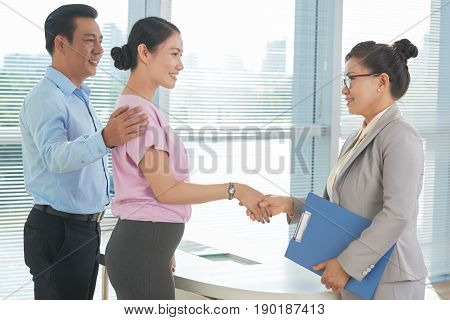 Asian mature realtor and couple shaking hands before meeting