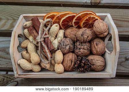Little Wooden Box With Walnuts, Groundnut Seeds, Cinnamon Sticks And Dehydrated Orange Slices