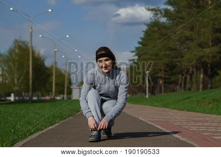 Woman Tying Shoe Laces. Female Sport Fitness Runner Getting Ready For Jogging Outdoors On Forest Pat