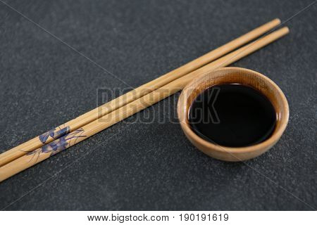 Close-up of chopsticks and soy sauce on stone table