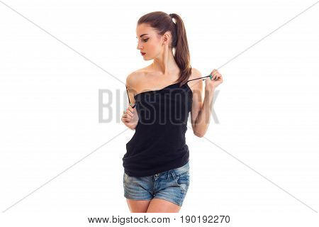 beautiful slender brunette stands before the camera in a black t-shirt unscrewing head isolated on white background