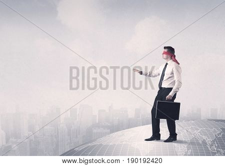 Young blindfolded businessman steps on a grey world map with a city in the background