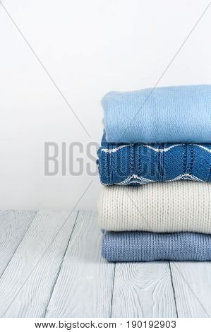 Knitted wool sweaters. Pile of knitted winter, autumn clothes on white, wooden background, sweaters, knitwear, space for text.