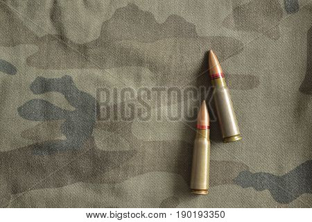 Two rifle bullets on military camo. Military ammunition