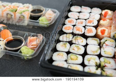 Close-up of various sushi rolls in platter with soy sauce