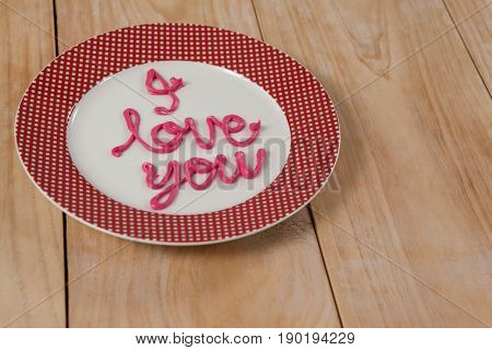 I love you text written with pink cream on plate on wooden surface