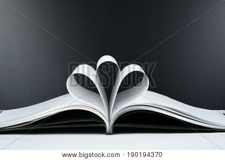 Old open hardback book, page decorate into a flower shape for love in Valentine's. love with open book heart
