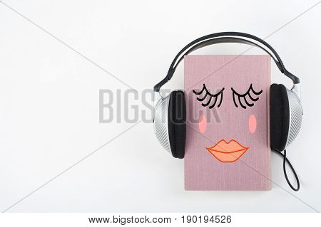 Audiobook on white background. Headphones put over pink hardback book, empty cover, copy space for ad text. Distance education, e-learning concept