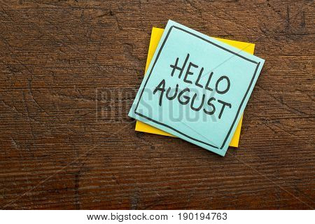 Hello August - handwriting on a sticky note against rustic wood