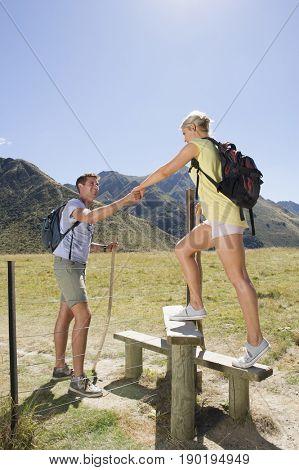 Caucasian couple climbing over fence