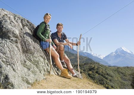 Caucasian couple leaning on boulder