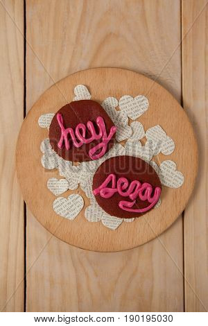 Cookies iced with pink cream displaying hey sexy on wooden surface