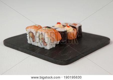 Maki, uramaki and nigiri sushi served in black stone slate against white background