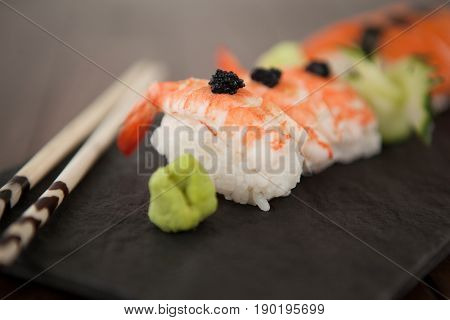 Close-up of nigiri sushi served with chopsticks in black stone slate on wooden table