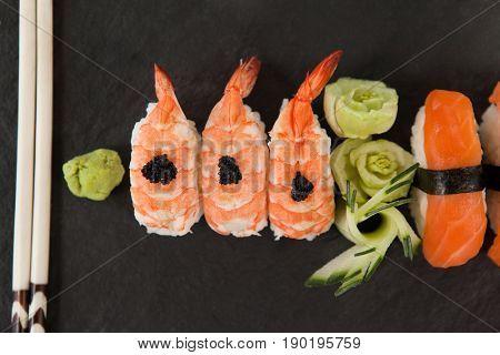 Close-up of nigiri sushi served with chopsticks in black stone slate